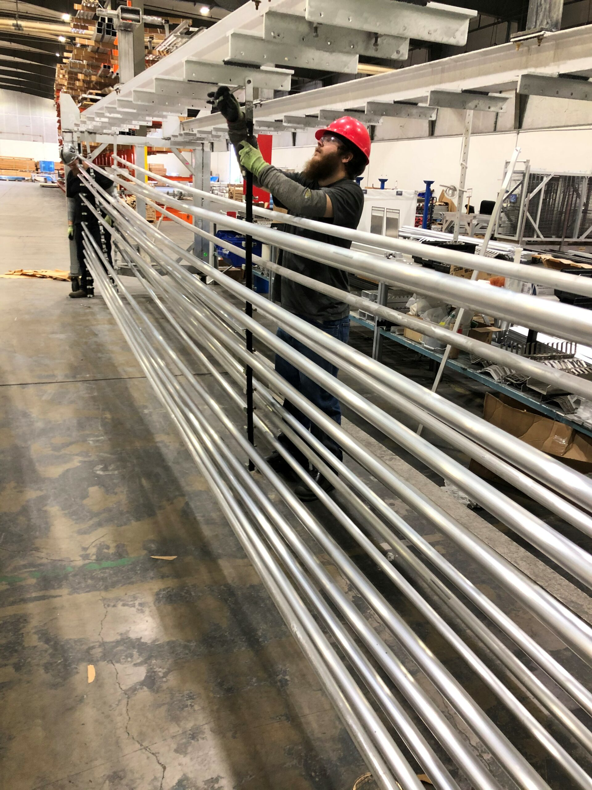 SAF Employee shows how parts are racked as the first step in anodizing